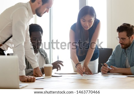 Focused diverse business executive team people designers architects with female asian leader manager discuss paperwork financial report brainstorm work together at group corporate office meeting