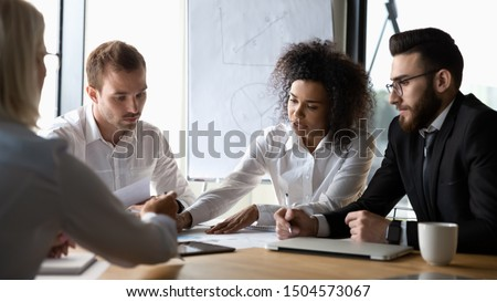 Focused diverse corporate business team participating at group brainstorming financial report discussion, analyzing paperwork, engaged in teamwork at office meeting lead by african woman company boss