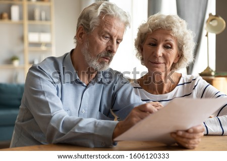 Focused elderly 70s married couple sit at table at home, husband holding papers documents spouses manage financial statement analysing medical insurance terms, bank account balance of family concept
