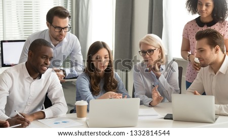 Focused employees group talk working together looking at laptop computer listen to colleague explain strategy at corporate business discussion, diverse coworkers team involved in brainstorm teamwork