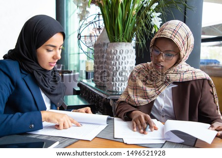 Focused female colleagues analyzing documents in cafe. Young Muslim business women reading papers. Document expertise concept #1496521928