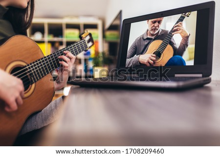 Focused girl playing acoustic guitar and watching online course on laptop while practicing at home. Online training, online classes. Stock photo ©