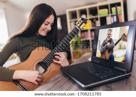 Focused girl playing acoustic guitar and watching online course on laptop while practicing at home. Online training, online classes. ストックフォト ©