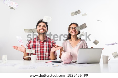 Focused Indian young couple accounting, calculating bills, discussing planning budget together using online banking services and calculator, checking finances