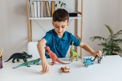 Focused kid playing with dinosaurs at home. Boy learning paleontology by dino toys at leisure. Concept of clever child and early education