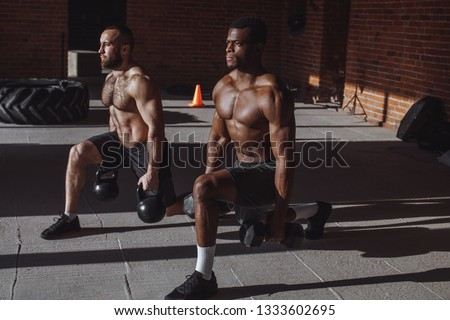 Focused male african and caucasian athletes showing determination and endurance exercising legs and back musculs during body core crossfit workout #1333602695