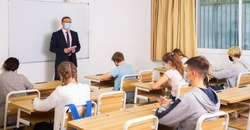 Focused male teacher in protective face mask giving lesson to teenage students in college. New life reality during coronavirus pandemic