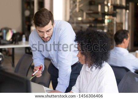 Focused male trainer or coach teach African American female intern explaining issue on laptop, team manager instruct woman trainee or help colleague with project on computer in coworking office