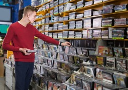 Focused man looking for interesting movies on shelves of CD shop