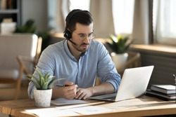 Focused man wearing headset writing notes, serious young student wearing glasses studying, looking at screen, watching webinar training, listening to lecture, mentor coach teaching online