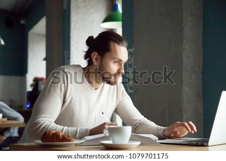 Focused man writing making notes studying with laptop in cafe, serious millennial student, businessman or entrepreneur using computer for e-learning and online education in public place concept