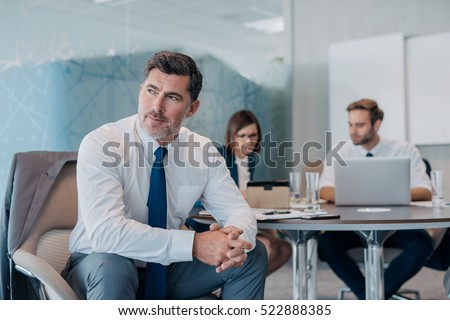 Focused mature businessman deep in thought while sitting at a table in an office with colleagues working in the background