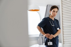 Focused mid woman doctor in medical suit fastening badge while standing at home