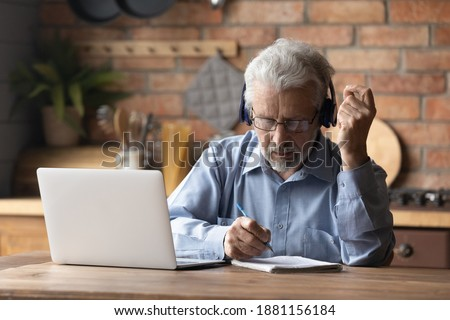 Focused middle aged mature man in glasses wearing headphones, involved in studying on online courses using computer applications. Concentrated older grandfather watching online webinar, writing notes. Photo stock ©