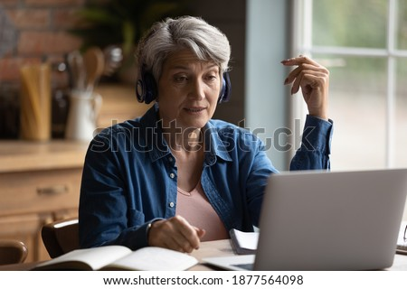 Focused middle aged mature woman wearing wireless headphones, involved in online communication with teacher using computer software video call application, older people and distant education concept.