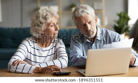 Focused middle aged retired family couple managing monthly budget, involved in financial paperwork, paying taxes online using e-banking computer application or calculating expenses together at home.