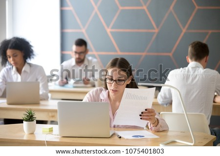 Focused millennial businesswoman working on laptop with graphs in coworking, serious intern or marketing sales manager holding document analyzing project report using computer in multiracial office