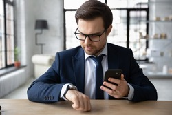 Focused millennial Caucasian male employee in suit look at hand watch clock checking time meet deadline. Serious young businessman hold use modern smartphone, synchronize gadget with smartwatch.