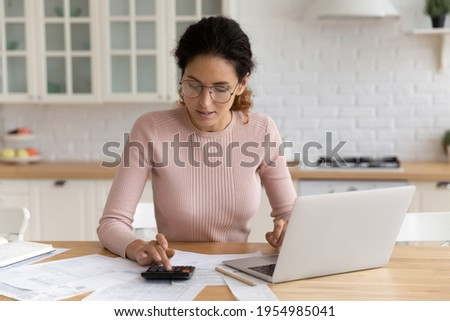Focused millennial latin woman auditor accountant manage paperwork at home office do calculation use pc to provide transaction. Young female student check tuition fee sum before pay in e-bank service Foto stock ©