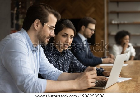 Focused millennial male intern look at laptop screen listen to skilled indian female mentor. Hindu woman experienced worker consult young man new employee help in computer work at corporate network