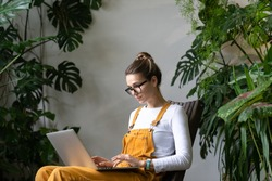 Focused millennial woman gardener in overalls watching educational webinar on laptop, writing blog or email, studying, remotely online work in her home garden surrounded by tropical plants. E-learning