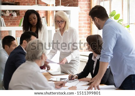 Focused multi-ethnic business executive team gathered for brainstorming lead by middle aged corporation boss do paperwork, analyzing financial report together at group corporate office meeting concept