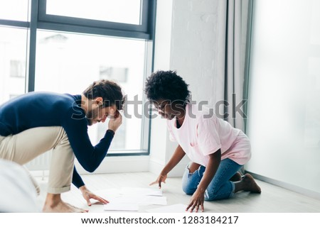 Focused multicultural small business partners develop future project, kneeling on floor in living room, looking at papers, thinking over how to make investments. #1283184217