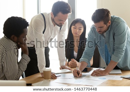 Focused multicultural team brainstorming on financial paperwork analyzing marketing report gathered at table in office, serious business people group brainstorm work in teamwork at corporate meeting