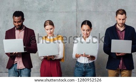 focused multiethnic casual businesspeople using laptops in waiting hall