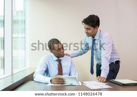 Focused new employee consulting mentor about data on tablet screen. Standing Indian in formal wear patting on back and instructing sitting Afro American with tablet. Mentoring concept