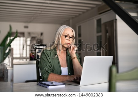 Focused old woman at home using laptop. Senior stylish entrepreneur with notebook and pen wearing eyeglasses working on computer. Serious lady analyzing and managing domestic bills and home finance.