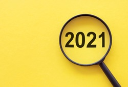 Focused on business concept. Magnifier glass with word numbers 2021 on yellow table. Business concept in new year. Search idea