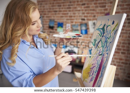 Stock Photo Focused painter and her painting