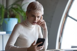 Focused pensive businesswoman looking at phone screen in office, worried serious female employee reading bad unpleasant news in email, having problem with smartphone, sitting at work desk