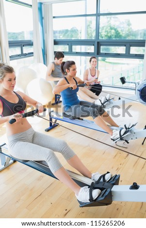 Focused people sitting at the row machine at the gym