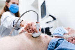 Focused photo of ultrasound scanner checking mature patient`s chest by female doctor in mask in the background