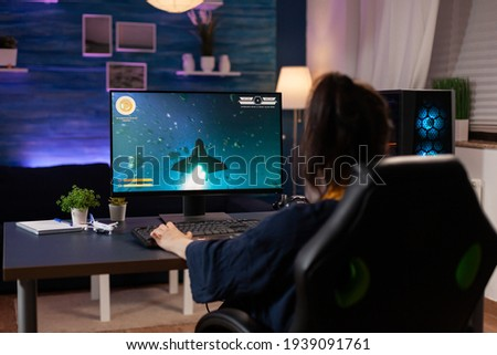 Focused player sitting on gaming chair in home studio and playing online videogames using RGB keyword. Professional pro player streaming online video game new graphics using powerful computer