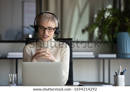 Focused pleasant 30s businesswoman in eyeglasses wearing wireless headphones with microphone, looking at laptop screen, holding video call negotiations meeting online with partners alone in office.