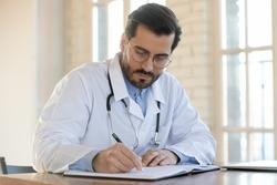 Focused 35s male doctor gp physician in glasses and white coat working with registry book, writing notes or recording healthcare treatment, sitting at table in office, casual medical worker workday.