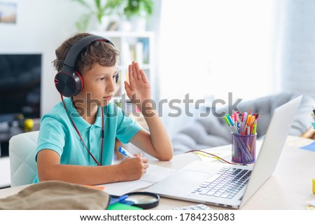 focused schoolboy boy wearing headphones uses laptop for distance learning during quarantine period. child raises his hand to answer lesson. e-education. Distance Learning, Home Learning. Stay at home
