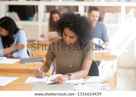 Focused serious african american female college high school student studying in multi ethnic classroom group writing essay in exercises book passing final exam test working on university assignment