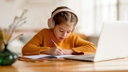 Focused serious elementary  little girl in headphones   making notes in notepad while communicating with teacher through video chat app during online education at home