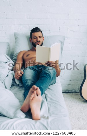 focused shirtless muscular man reading book during morning time in bedroom at home