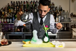 Focused skilled young ethnic mixologist pouring liquid from stainless pot into jar with foam while preparing contemporary molecular cocktail in bar