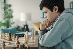 Focused smart boy playing chess at home, he is thinking and looking at the chessboard