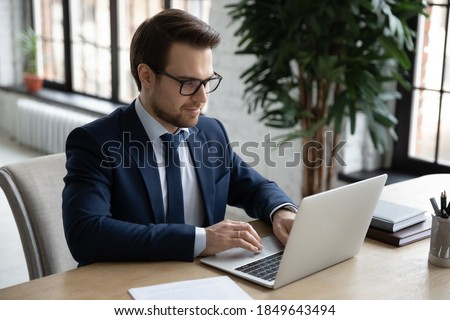 Focused smiling young businessman in formal wear looking at computer screen, working on project online, web surfing information, analyzing statistics, watching webinar or holding distant meeting. Foto stock ©