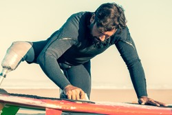 Focused sporty man in wetsuit wearing artificial limb, waxing surfboard on sand on ocean beach. Artificial limb and active lifestyle concept
