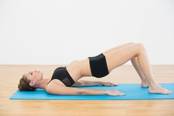 Focused sporty woman lying on blue exercise mat doing exercises in sports hall