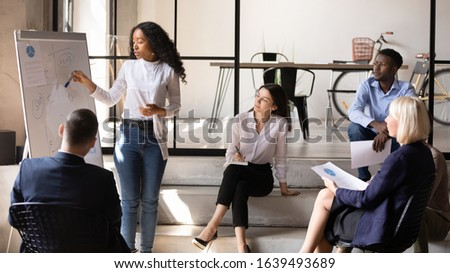 Focused staff comfortably settled in modern office attending at workshop in informal setting listen african trainer teaching audience share ideas finance plan use flip chart, mentoring seminar concept