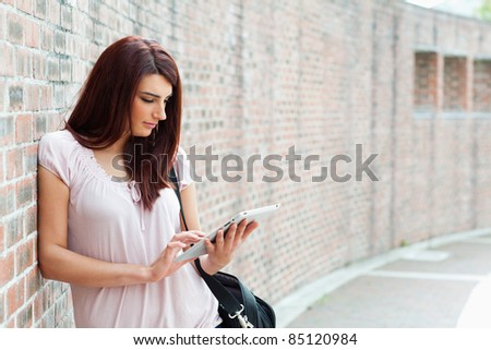 Focused student using a tablet computer outside a building - stock photo